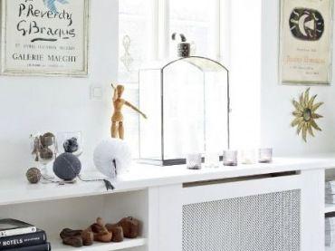 Biały pokój wiele zyskuje dzięki pojedynczym dekoracjom. Niektóre z nich wyeksponowano na długiej półce nad niską...