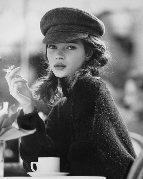"""Outtake of Kate Moss by Kate Garner:  """"She turned up for the shoot wearing a very small denim mini skirt, her boyfriend's underpants (she hadn't been home from the night before) and a little vest top. She managed to look adorable and chic … the hat and sweater picture was later in the day. Prob the second cigarette and cup of tea in a local cafe."""""""