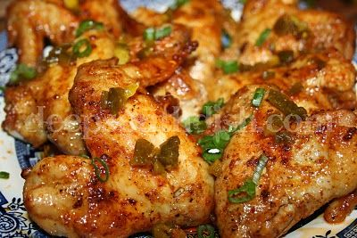 Oven baked hot wings made with a buttery Louisiana hot sauce and garnished with sliced green onion and chopped jalapenos.