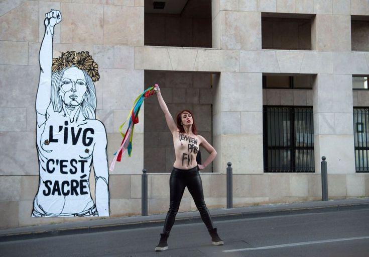 """Una activista femenina con una inscripción pintada en su pecho, posa frente a una obra de arte con una inscripción que se traduce como """"IVG (Ley sobre el aborto voluntario) es sagrado"""" en Marsella, Francia."""