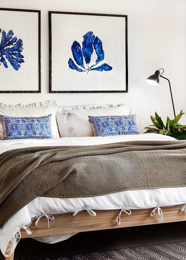 Neutral bedroom with a pop of blue in the art and pillows