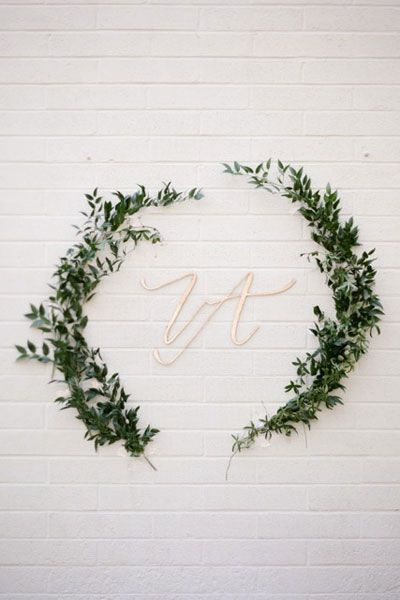 Dark green olive branches draw the eye to gold initials for a bold effect against a white brick wall.