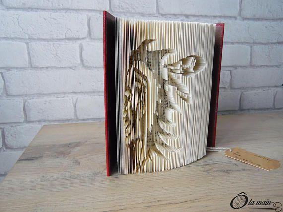 La collection A Livre Ouvert est une série de livres doccasion transformés en objets de décoration via plusieurs techniques (découpage, pliage ou décou-pliage). Chaque page est découpée et/ou pliée à la main pour donner vie à un motif.  Le modèle La plume de lIndien est un livre découpé et plié pour représenter le visage dun indien dAmérique. Le livre possède une magnifique couverture rouge et or. VENDU SEUL