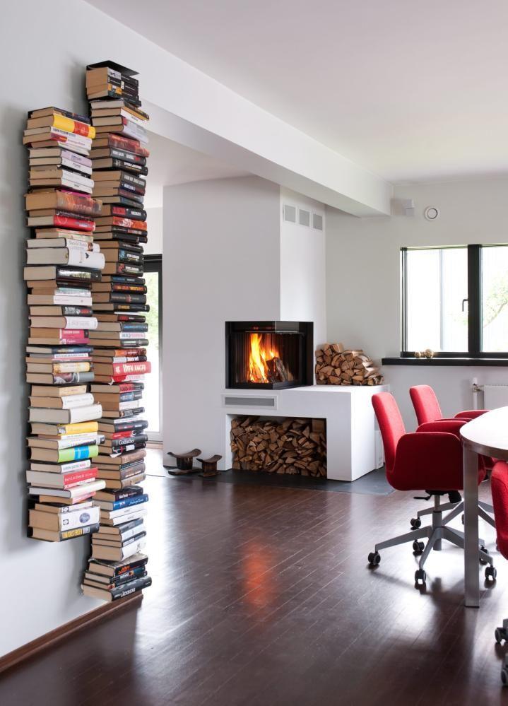 SYSTEMATISERT ROT: Bøkene og vedstabelen utgjør et myldrende element i et ellers rent og strengt interiør. Gulvet er slipt og beiset. Vinduskarmene er malt svarte og bidrar til å ramme inn utsikten. Hyllene Ptolomeo er fra Opinion Ciatti.