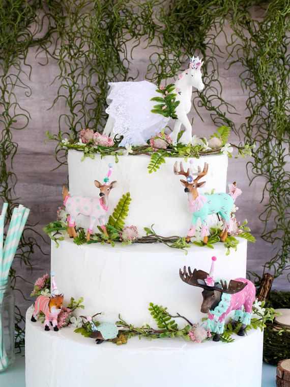 Enchanted Forest Birthday party for teenager. Unicorn cake topper, and forest animal toppers on birthday cake. Simple floral on the white cake makes a beautiful statement. Unique customized cake toppers. Forest animal theme, woodland theme, and enchanted forest theme parties.