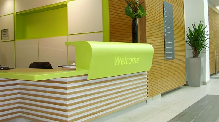 'Welcome' letters on green reception desk by Space3.co.uk