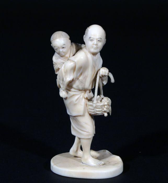 Ivoren okimono van man met kind - Gesigneerd - Japan - Eind 19e eeuw (Meiji-periode)  Ivoren kimono van zeer hoge kwaliteit met een prachtig patina. De gezichten handen en voeten zijn bijzonder fraai gesneden. Hoogte: ca. 10 cmHet beeld heeft een krimpscheurtje op het voetstuk (zie foto 18) zoals gebruikelijk bij beelden van deze leeftijd. Verder in uitstekende conditie. Geen gebreken. Het beeld is gesigneerd aan de onderzijde.DIT OBJECT WORDT ALLEEN BINNEN EUROPA VERZONDEN.THIS OBJECT WILL…