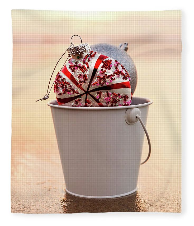 Fleece Blanket featuring the photograph Christmas Bucket by Evgeniya Lystsova. Closeup of Christmas Decorations Collected in a White Bucket on the Beach at Sunset time, Holiday Concept. Our Luxuriously soft blankets are available in two different sizes and feature incredible artwork on the top surface. Get Your Home Holiday Ready! #Christmas #Sunset #Blanket #Gifts #HomeDecor #InteriorDesign