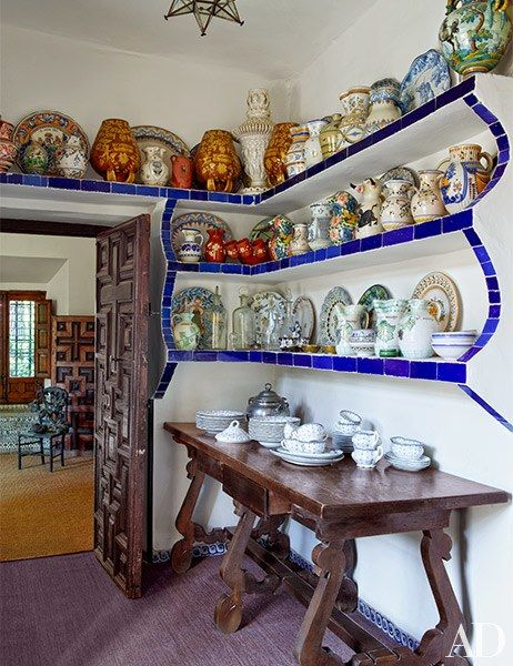 Iberian pottery from the 16th through 19th centuries crowds shelves in the kitchen office | archdigest.com