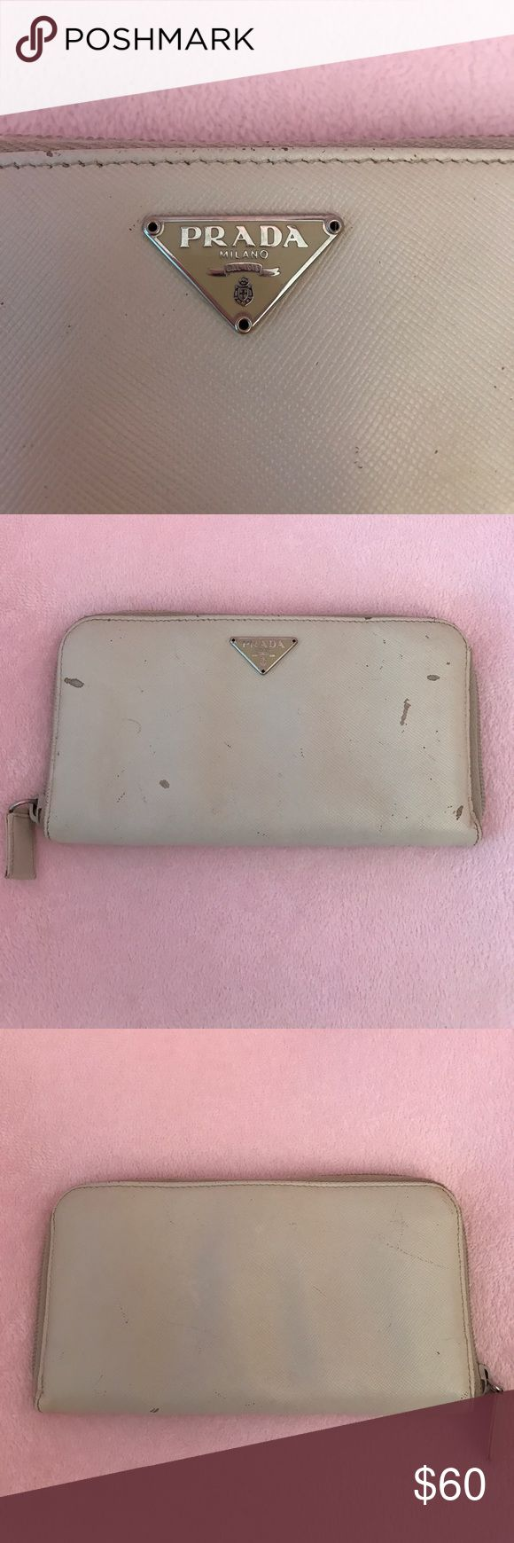PRADA wallet Used 100% authentic Prada wallet. As you can see in the photos this wallet is well loved. There are some obvious signs of wear. Unfortunately my water bottle opened in my purse and soaked my wallet so there is warping. Overall still has a lot of life left in it. Zippers work perfectly. Price reflects condition. Price is firm I will not except any offers. Thank you! NO TRADES! Prada Bags Wallets