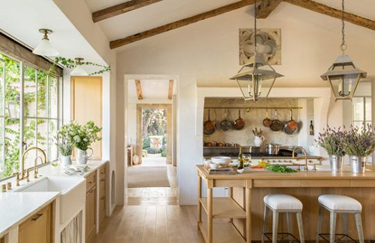 Inspired by French farmhouse kitchens and Belgian cabinetry, Brooke and Steve Giannetti designed a large, white oak center island for dining and prep work in their Ojai, California home. The stone quatrefoil and copper pots are both European antiques.