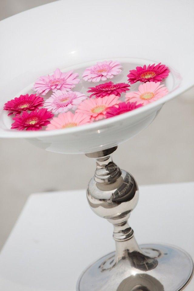 roze drijvende gerbera's in schaal met zilveren poot als decoratie