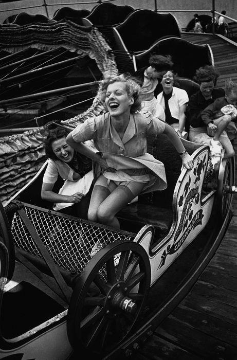 by Kurt Hutton -   The wind catches a young woman's skirt revealing her garters as she climbs out of an amusement ride car at the Southend Fair. 1938 Southend-on-Sea, Essex, England, UK.