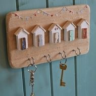 Seaside beach hut key hooks, hand painted and handmade from driftwood and reclaimed materials. With white wash huts, colourful driftwood door and tiny bunting above. Would also be great as jewellery hook or used in a kitchen for tea towels. It comes wi...