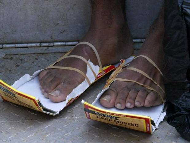 Jeremiah Ward wears his makeshift shoes made of cigar boxes after he was rescued in the Ninth Ward on Aug. 30, 2005, in New Orleans during Hurricane Katrina. This photo was included in the winning entry of the 2006 Pulitzer Prize for Breaking News Photography. Photo: Irwin Thompson.