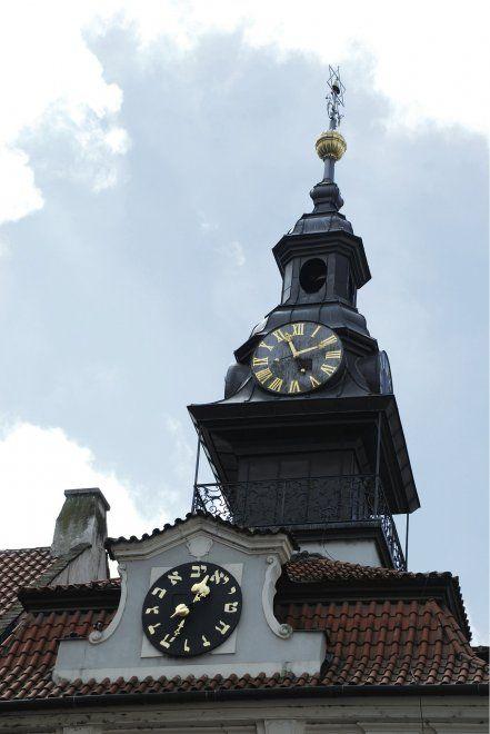 """""""Un orologio che gira in senso antiorario""""  Finanziato dal vecchio borgomastro del ghetto ebraico (Mordechaïm Maisel), il municipio del ghetto (Židovská radnice), all'angolo di via Maiselova e via L'ervenä, fa parte dello stesso complesso che comprende la Grande Sinagoga, costruita nel 1577. La sua ricostruzione in stile Rococò risale al 1754. L'edificio ha un orologio con due quadranti: uno classico e l'altro con le lettere dell'alfabeto ebraico al posto dei numeri tradizionali. In ebraico…"""