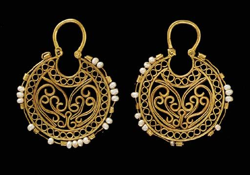 A PAIR OF BYZANTINE GOLD EARRINGS   Circa 6th-7th Century B.C.   Each crescentic in form, composed of strips of rectangular wire arranged in various spirals and figure-8 loops, the perimeter with nine ribbed tubes through which passes a plain wire threaded with pearls, a hinged arching ear wire above