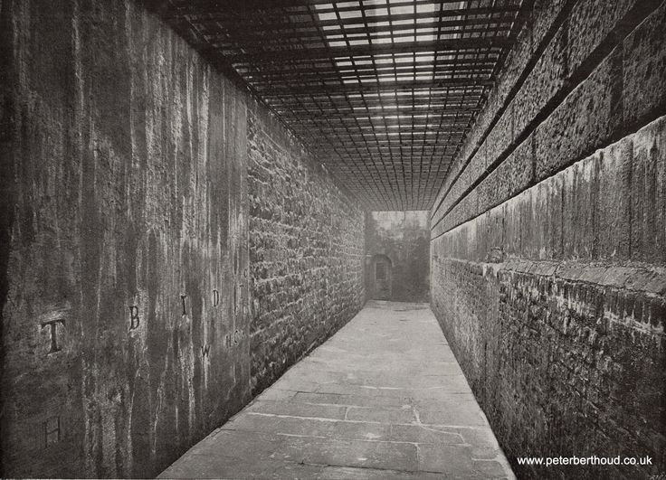 """The """"graveyard"""" at Newgate Prison is a very grim-looking burial-place, which primarily serves the purpose of a passage from the gaol to the Old Bailey. Those who within the precincts of the prison have paid the extreme penalty of the law are buried under the flagstones, lime being enclosed in the coffins. On the walls on either side are the initial letters of the murderers surnames, and by this means the places of burial are recorded, though neither dates nor names are now added."""