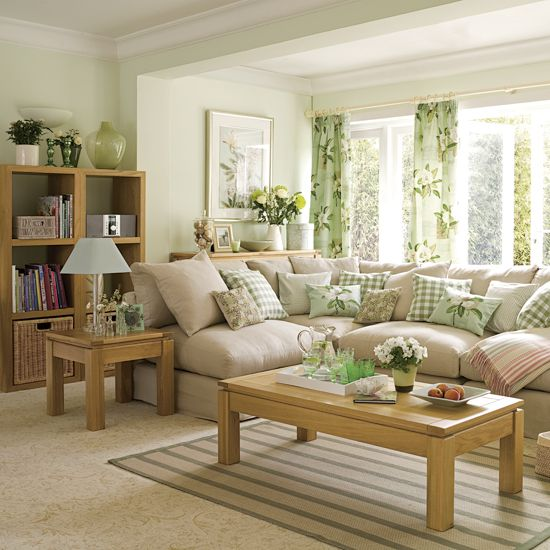 The garden fresh green of the curtains has been repeated around the room to create a living room with an easy-to-live-with hit of colour. Jugs of flowers and botanical prints add summer touches to compliment the green fabric. The cube storage unit is grea