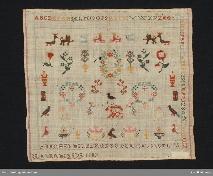 alfabet A-Ø øverst og bokstaver og tall nedorver høyre side, symmetrisk ordnede småmotiver, blomsterkrans, hjerter, fugler, dyr, timeglass m.m.