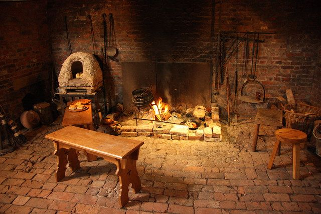 One of the fireplaces in Gainsborough Old Hall medieval kitchen with a fire cooking garlic broth in a cauldron