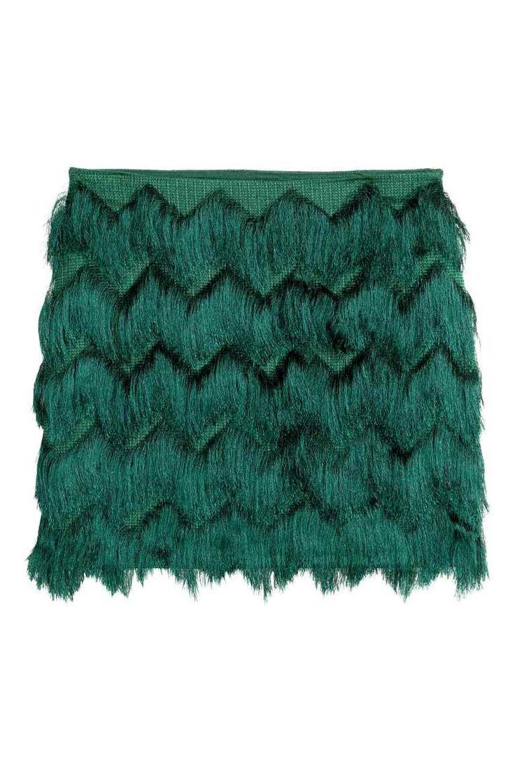 35€ Jupe à franges: Jupe courte avec franges coupées de façon à former un motif zigzag. Fermeture à glissière apparente dans le dos. Doublée jersey.