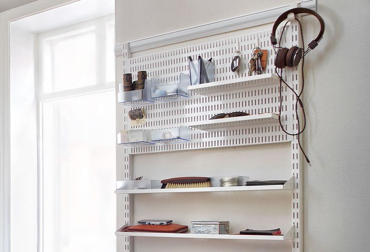 Elfa storage board with hooks and metal shelves for keys, sunglasses, earphones and more.