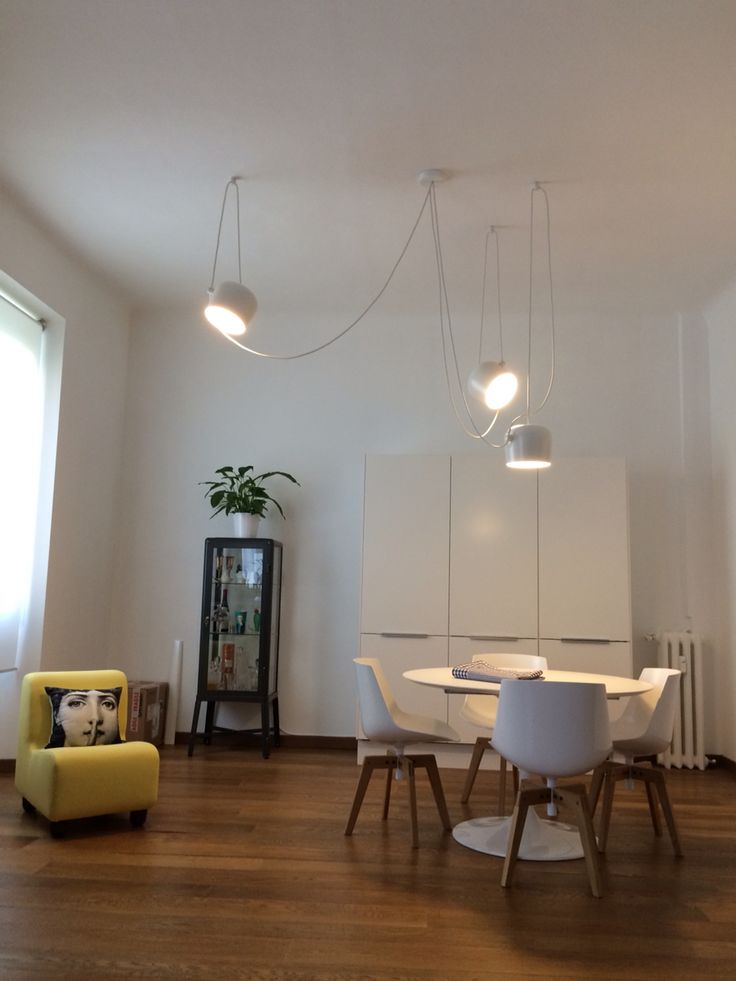 FLOS AIM pendant lighting brightens this minimalist space with yellow accents.