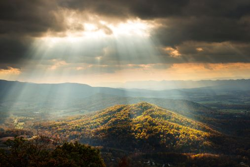 Stock Photo : Sunlight Shining Through Clouds onto Hills