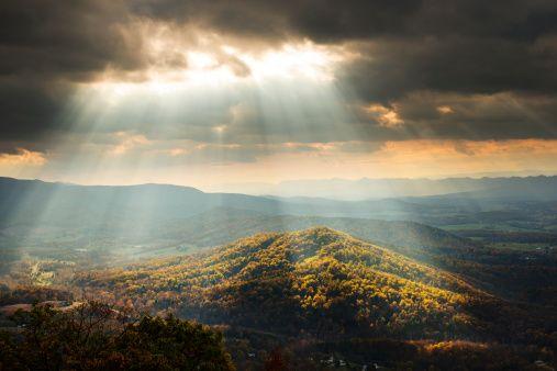 Stock Photo : Sunlight Shining Through Clouds onto Hills