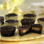 Peanut Butter Chocolate Cheesecake Cups - A chocolate wafer crust forms the base of each peanut butter-filled chocolate cheesecake cup.
