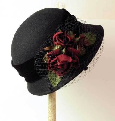 This classic wool cloche is trimmed with deep wine colored roses and a pouff of bird cage veiling.