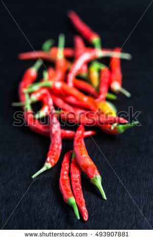 handful of red hot chili peppers close up over black background