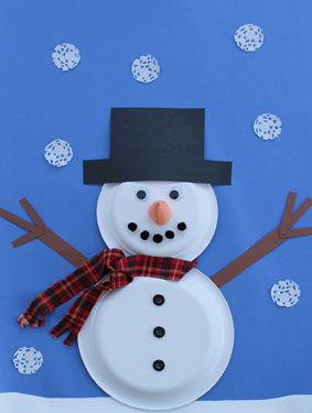 A snowman made of paper plates, the snowflakes are cut from doilies.