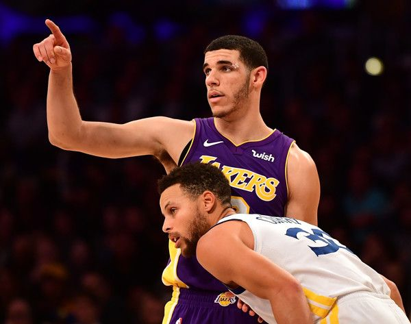Lonzo Ball Photos - Lonzo Ball #2 of the Los Angeles Lakers signals as he is guarded by Stephen Curry #30 of the Golden State Warriors during a 127-123 Warriors win in overtime at Staples Center on November 29, 2017 in Los Angeles, California. - Golden State Warriors v Los Angeles Lakers