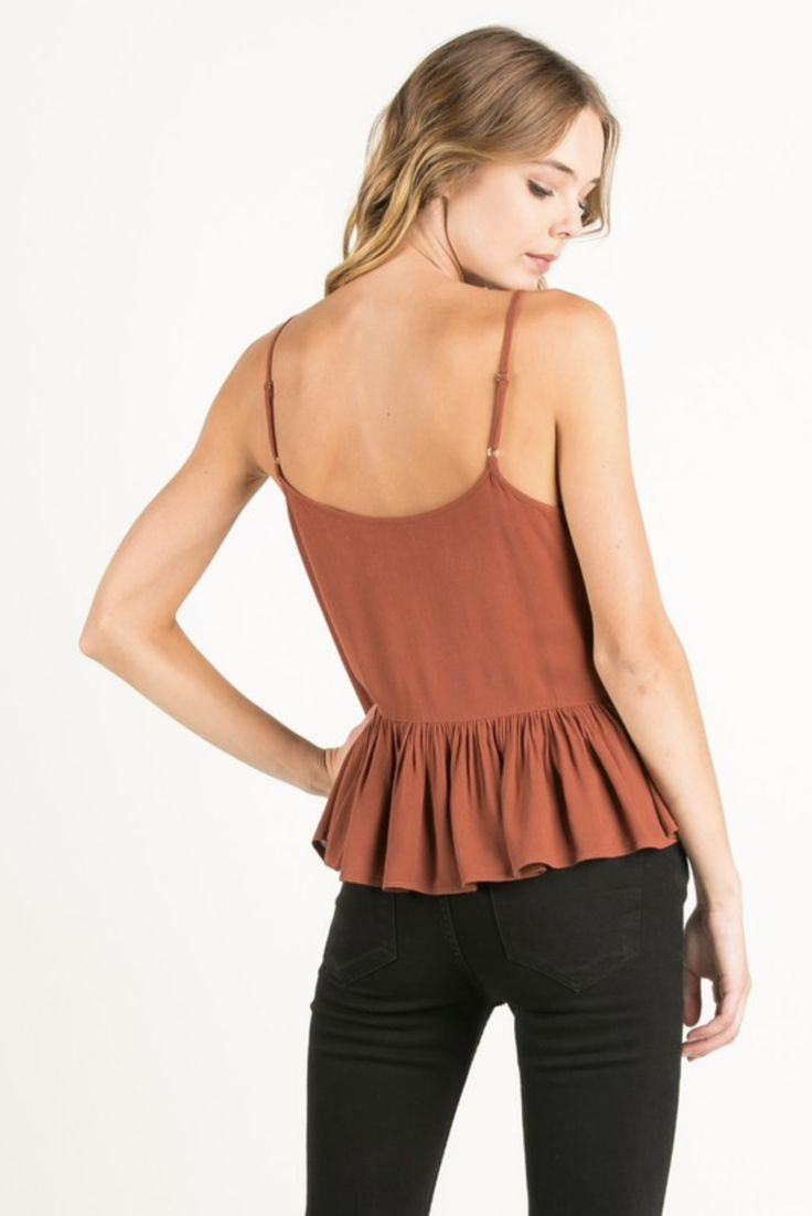 - Slightly cropped peplum blouse - Lace inset with cut-out detailing down the middle - Adjustable spaghetti straps - Available in Cream, Olive, or Rust - 100% Rayon - Imported