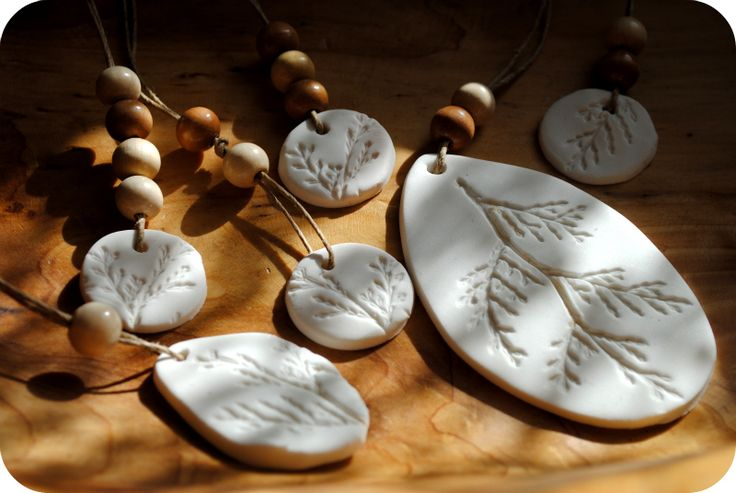Clay Nature Impressions. I love the white and natural colored beads. Made with white Sculpey.  Good slide idea.