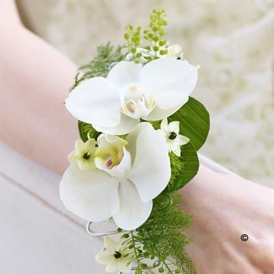 Rich in exquisite detail, this stunning wrist corsage is a beautiful style statement. Two exotic white orchids are complemented with perfect little ornithogalum flowers, deep green leaves and delicate fern.   Price: £ 24.99
