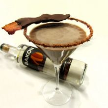 Bakon Chocolate Martini - CoCo Pig  The smokiness of the bacon enhances chocolate in ways you won't believe!  • 2oz Bakon Vodka  • 2oz chocolate liqueur  • 1oz Irish cream  • A splash of cream    Combine in a cocktail shaker and shake with ice. Strain and pour into a sugar-rimmed martini glass.