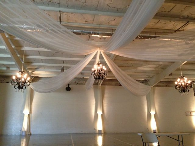 white ceiling draping with rustic chandeliers and uplighting to create a clean and simple reception.
