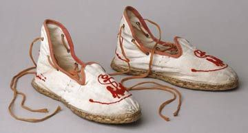 Pair of embroidered with linen espadrilles with cotton jute soles and cotton laces, 1910. Worn by Emily Tinne on her honeymoon in Ireland. Matches the embroidered red-orange wool serge bathing suit with wool braid trim and orange cotton sateen bathing cap.
