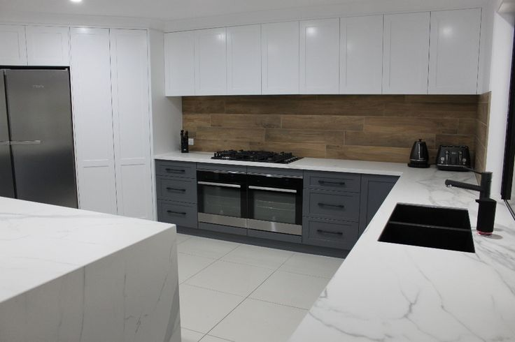 Recently completed job in Ripley - Benchtops - 40mm Caesarstone Calacatta Nuvo, Black Moritz Handles and Timber Look Backsplash www.everythingcabinets.com.au