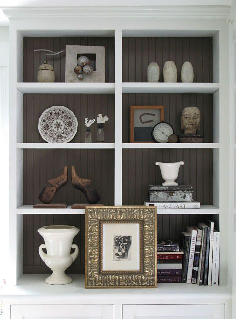 Paint the back of the bookcase a darker color. Makes the white and all of the objects stand out more. Really love this look