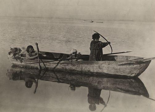 Alacaluf Indian children row their boat off Tierra del Fuego. Chile