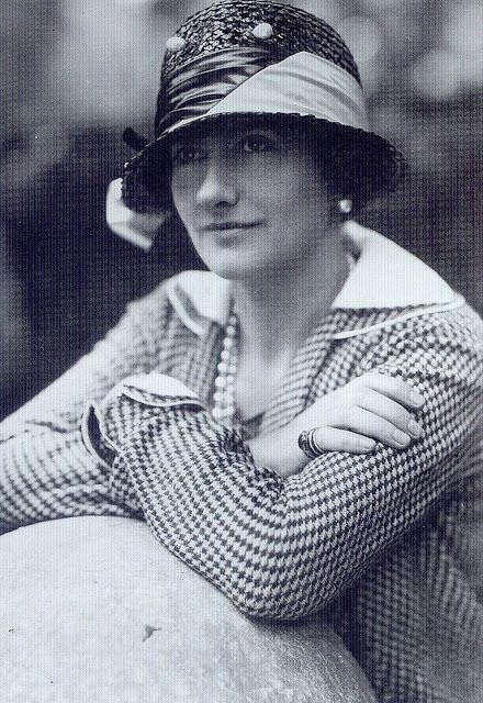 """""""This picture was taken in 1929, when Coco was forty-six, the year in which she opened an accessories boutique attached to her Paris salon. The pearls on the pin trimming her straw hat are extra large. Chanel played with oversized costume jewelry that did not pretend to be real."""""""