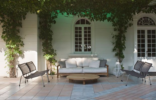 Grandi cuscini bianchi e telaio in legno chiaro per il grande divano che accoglie gli ospiti dell'albergo