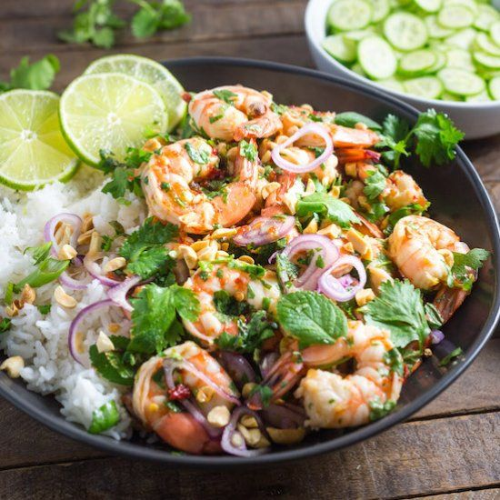 A healthy shrimp salad with a sweet and sour Thai dressing, topped with fresh herbs and crunchy roasted peanuts.