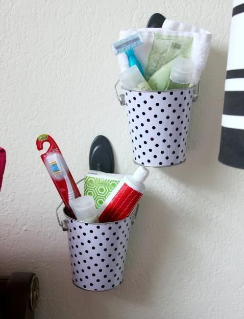 Install some tin buckets on your bathroom wall. You can design them to your taste -- polka dots, stripes or plain. They're perfect tools to hold your brushes, toothpastes, shaves and other trinkets.
