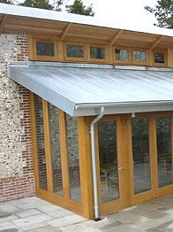 Zinc roof guttering sits well with timber doors