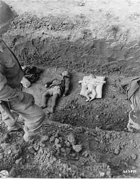 Photograph from the National Archives, courtesy of USHMM Photo Archives.    An American soldier stands above the corpses of children that are to be buried in a mass grave dug by German civilians from the nearby town of Nordhausen. (April 14, 1945)